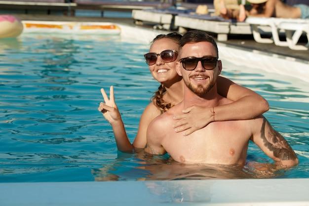 夏休み中にスイミングプールで楽しんで幸せな若いカップル