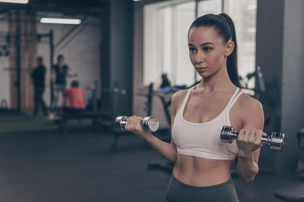 美しいフィットネス女性ジム、コピースペースでトレーニング