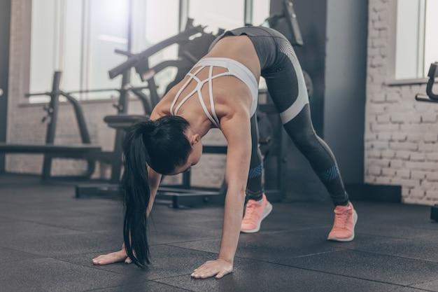 ジムでのトレーニングの前に彼女の体をストレッチ暗い髪のフィットスポーツウーマン、コピースペース