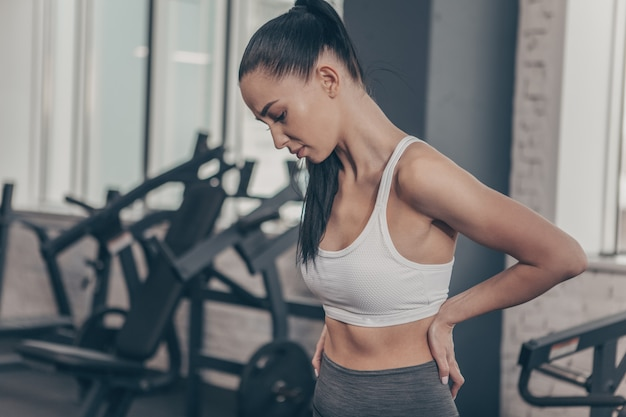 ジムでのトレーニングの後の背中の痛みを持つ運動美人