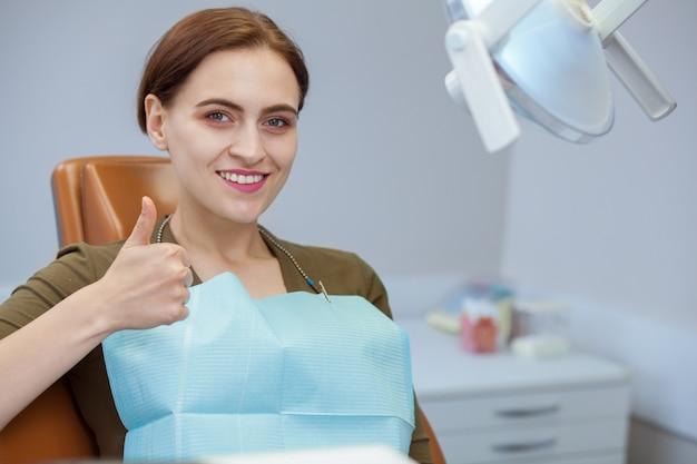 歯科用椅子に座って、親指を現して笑って幸せな美しい女性