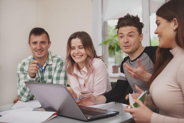 大学の教室で一緒に勉強している若者のグループ