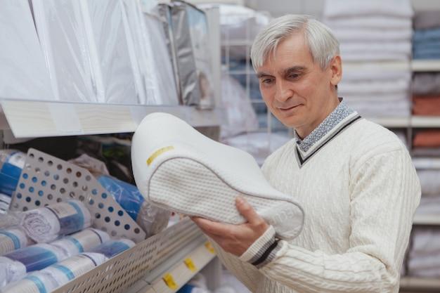 Пожилой мужчина делает покупки в магазине товаров для дома