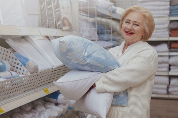 Пожилая женщина, покупки в мебельном магазине
