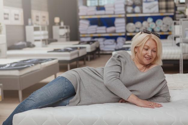 Зрелая женщина, покупки в мебельном магазине