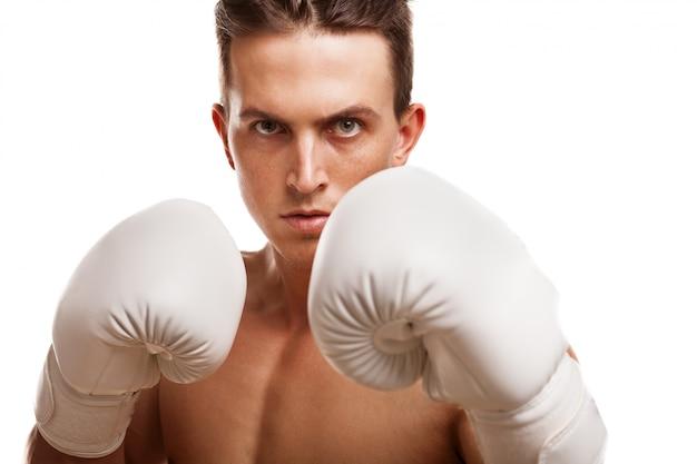 Крупным планом жестокий мужской боксер, подняв кулаки в боксерских перчатках