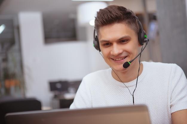 Молодой человек играет в видеоигры онлайн, в наушниках