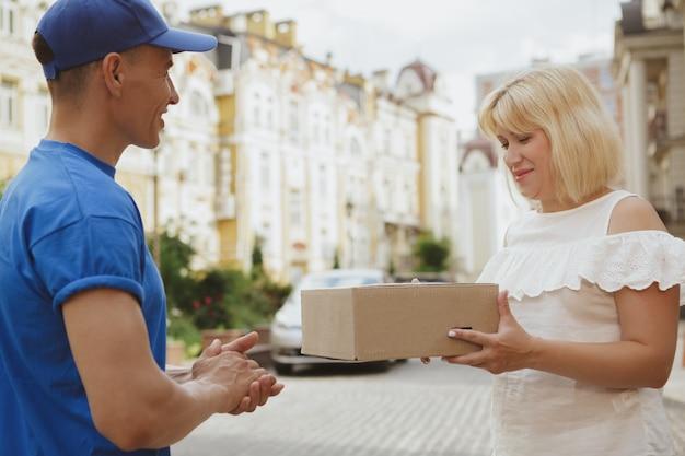 街の通りに小包の段ボール箱で若い陽気な配達人