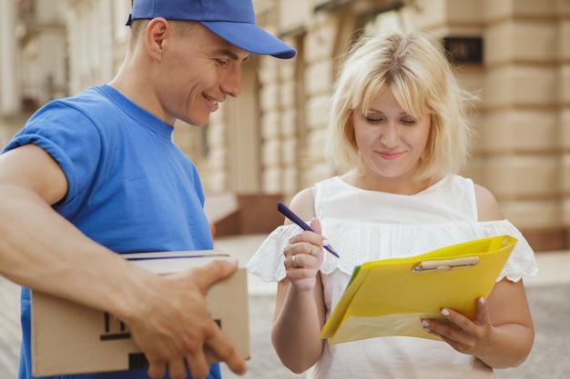 Молодой веселый доставщик с посылкой из картонной коробки на улицах города