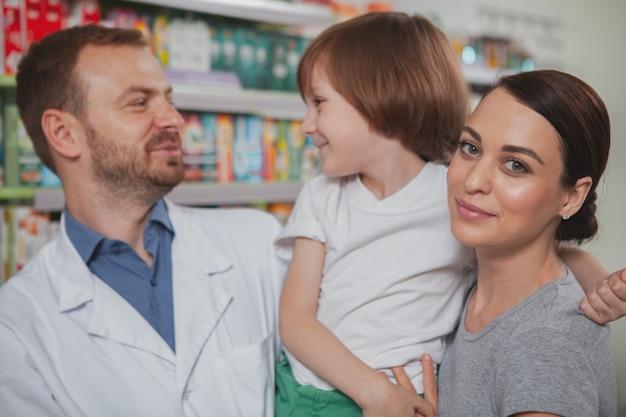 美しい女性が彼女の幼い息子とドラッグストアで買い物