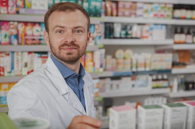 Веселый зрелый мужской фармацевт в аптеке