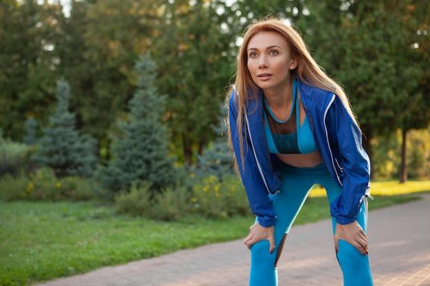公園で走っている若い美しいスポーツウーマン