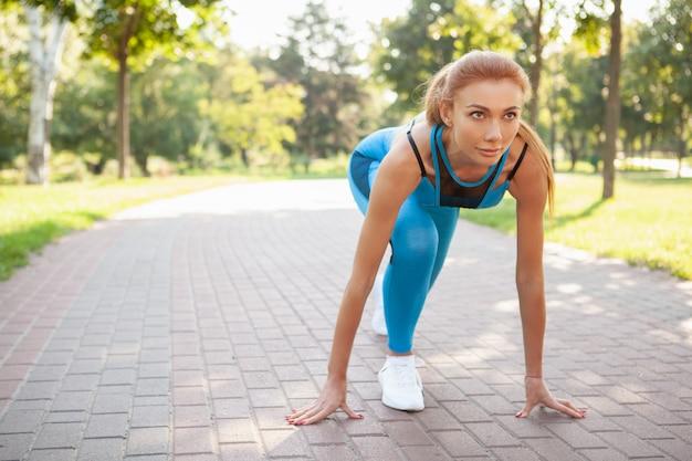Великолепная спортивная женщина работает в парке по утрам