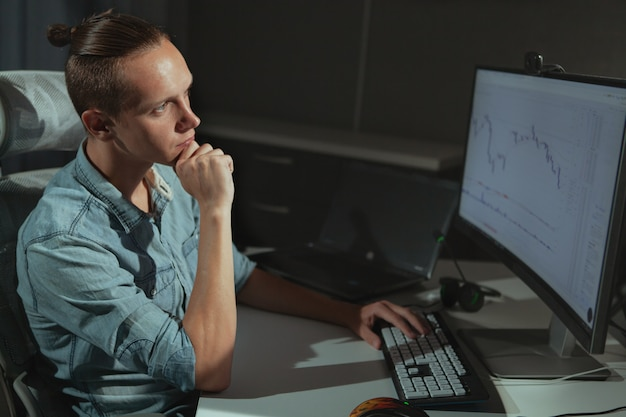 Молодой мужчина фрилансер, работающий поздно ночью