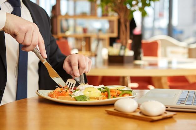 カフェで朝食を食べて実業家のクローズアップをトリミング