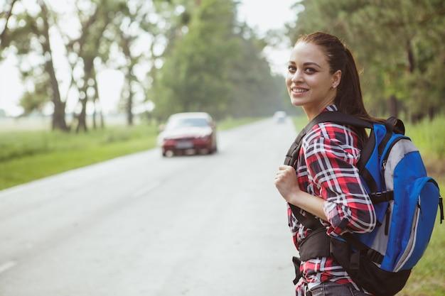 田舎でヒッチハイクする素敵な若い女性