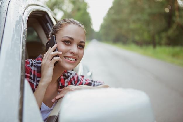 彼女の車のロードトリップに素敵な若い女性