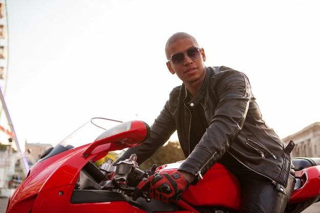 Африканский человек на спортивном мотоцикле в городе