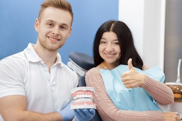 Красивый молодой мужской дантист демонстрируя форму зубов