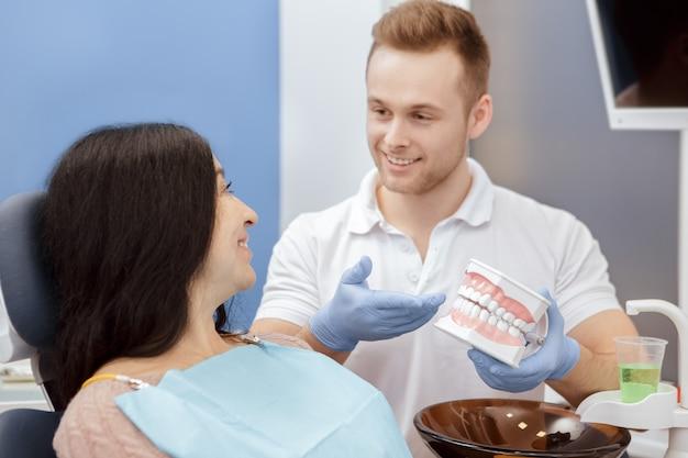歯型を示すハンサムな若い男性歯科医