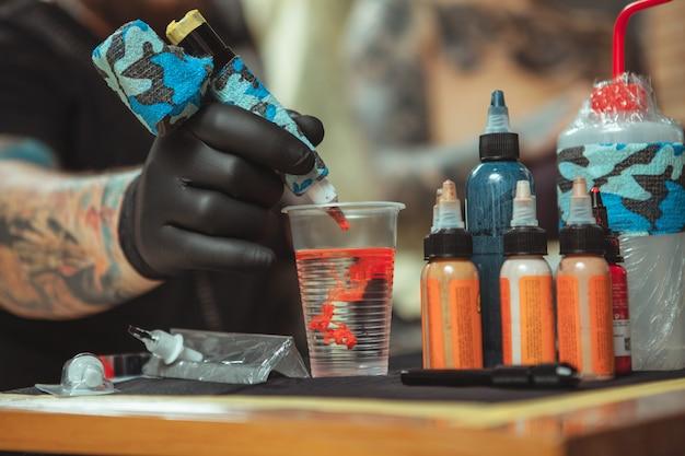 Профессиональный татуировщик делает новую татуировку для своего клиента