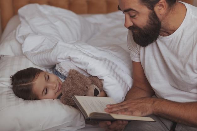 彼の小さな娘と一緒に家で休んで成熟したひげを生やした男