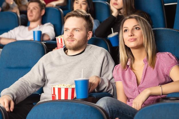 映画館で若い陽気なカップル