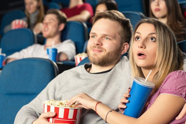 映画館で一緒に映画を見てハグする若いカップル