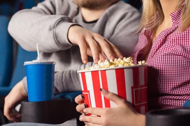 ポップコーンバケツからポップコーンをつかむ映画を見ているカップル