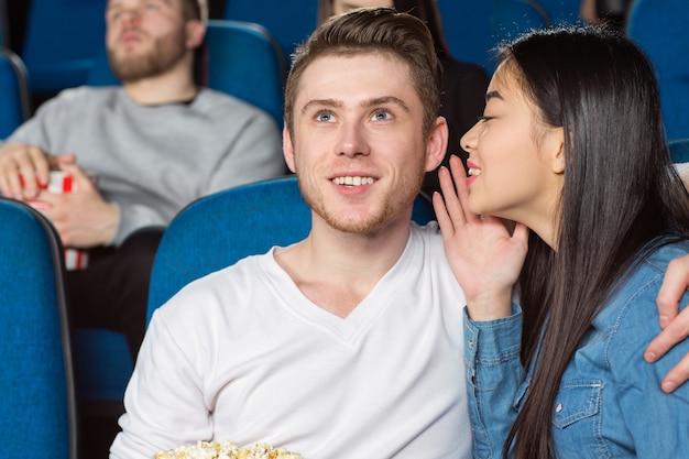 映画館でコメディ映画を見ながら彼女の陽気な笑顔のボーイフレンドにささやくアジアの女性