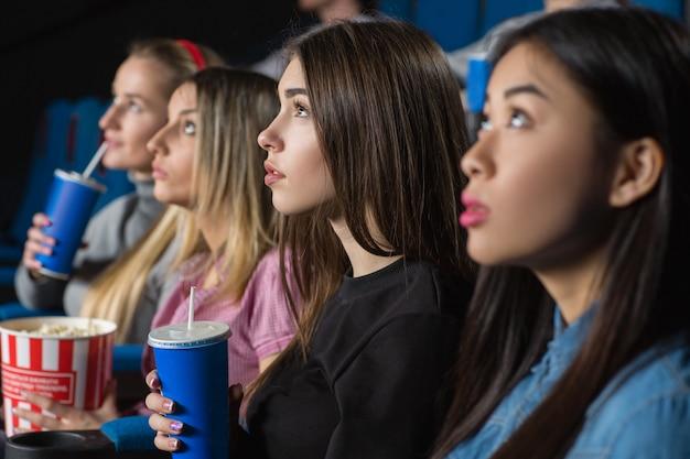 映画館で一緒に映画を見ている女性の友人のグループ