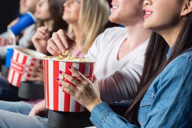 映画館で彼の女性の友人からポップコーンをつかむ男