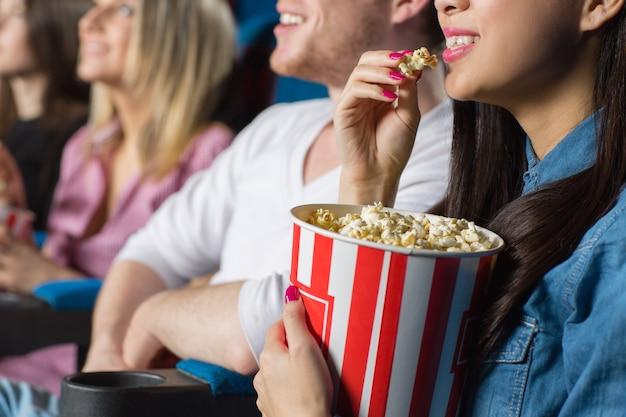 映画館で彼女の友人と映画を見てポップコーンを食べる若い女性