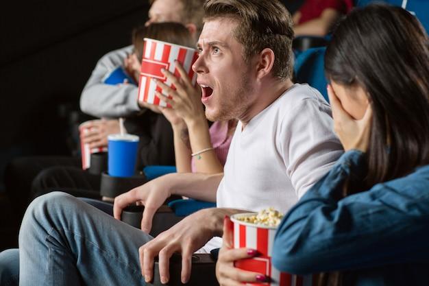 地元の映画館で彼の友人のグループと怖い映画を見て非常にショックを受けた若い男