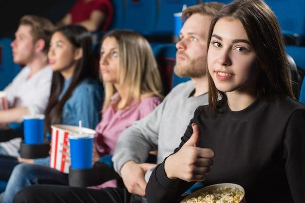 地元の映画館で友達と映画を楽しみながら親指を現してブルネット