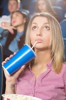 映画館で映画を見ている彼女の飲み物を飲む若い女性