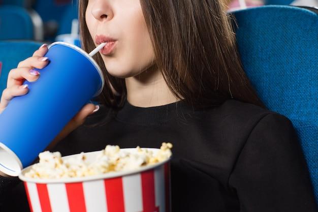 映画館でストライプポップコーンバケツを保持している女性の飲酒