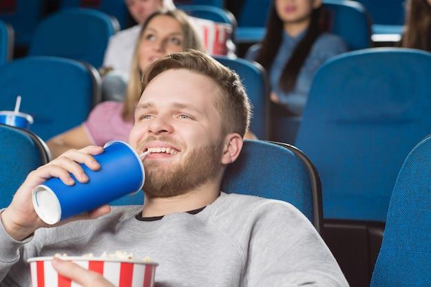 映画館で映画を見て元気よく笑顔のポップコーンのバケツを持って飲むハンサムな男