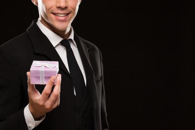 ギフト用の箱を持つハンサムなロマンチックな男