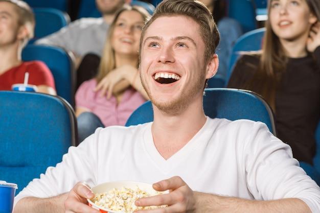 地元の映画館でコメディ映画を見ながら笑っている若い興奮した男