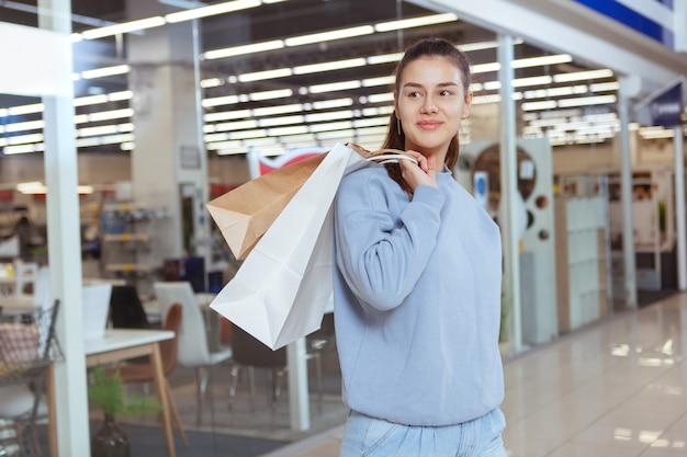 幸せな若い女性笑顔、元気に目をそらして、ショッピングモールで買い物袋を運ぶ