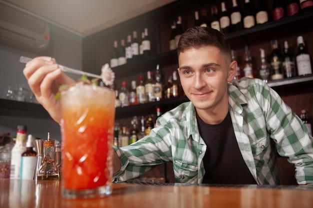 ハンサムな幸せなバーテンダーは、バーでの作業を楽しんで、クライアントのカクテルを飾ります