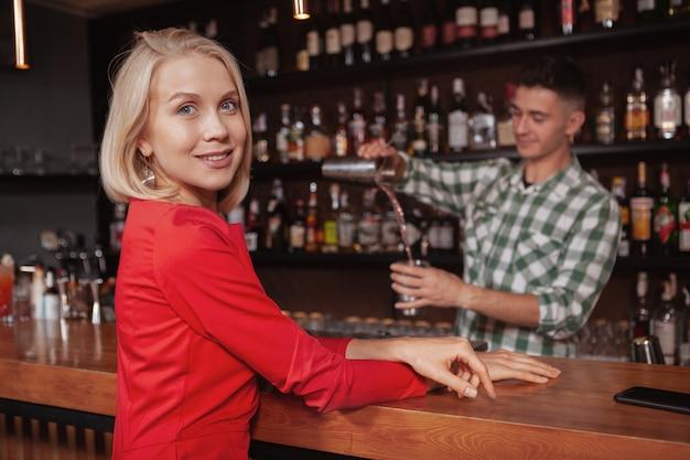 バーで彼女のカクテルを待って、カメラに笑顔美しい幸せな金髪女