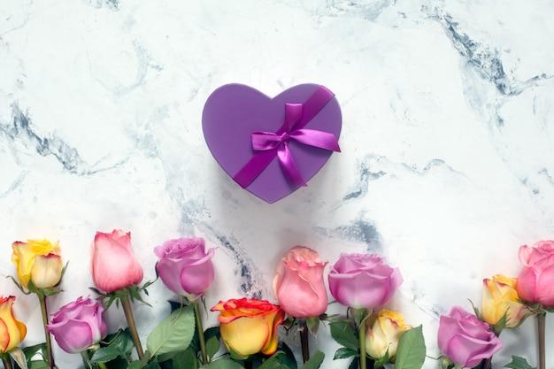 Фиолетовые и желтые розы, коробка присутствует на белом фоне