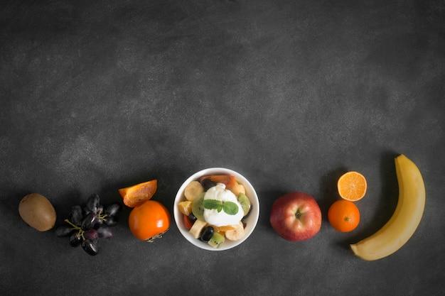 黒い黒板にミントと健康的な新鮮なフルーツサラダのボウル