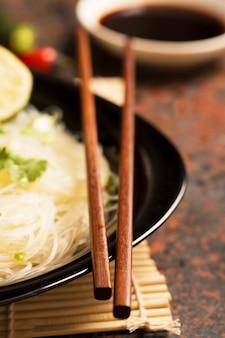Китайские палочки на черной тарелке
