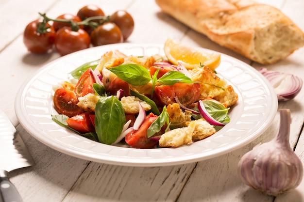 イタリアの前菜サラダ、トマト、パン、バジル