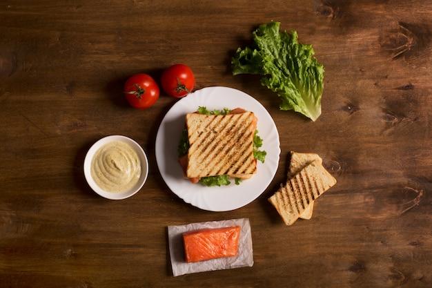 Клубный бутерброд, приготовленный с рыбой на деревянной доске