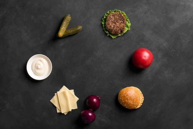 Бургер из говядины с салатом и соусом на черной доске