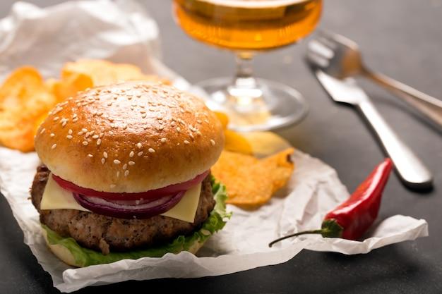 Гамбургер с мясной котлетой. картофельные чипсы и пиво
